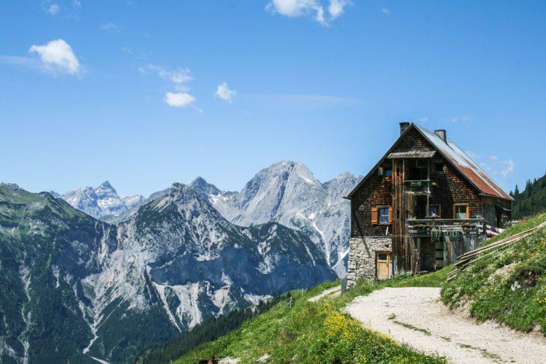 Die Plumsjochhütte mit den Karwendelbergen im Hintergrund