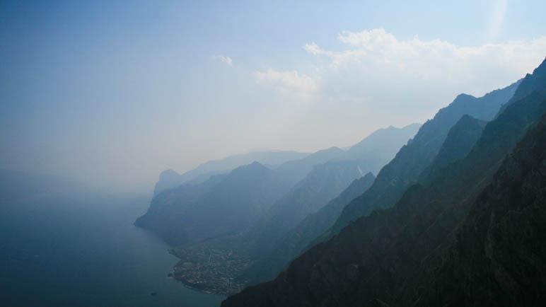Die Berge des westlichen Gardasee-Ufers verlieren sich im Dunst. Unten am Ufer sieht man den Ort Limone.
