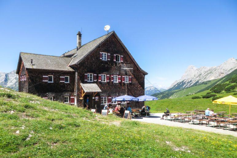 Die Falkenhütten steht auf einer Anhöhe inmitten von Wiesen vor der Laliderer-Felswand