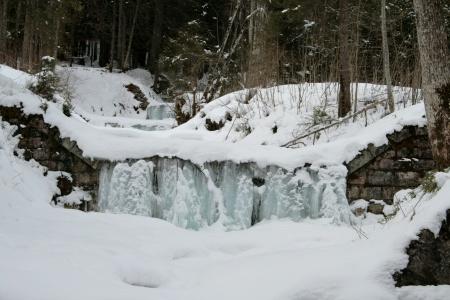 Gefrorener Wasserfall am Rand des Weges