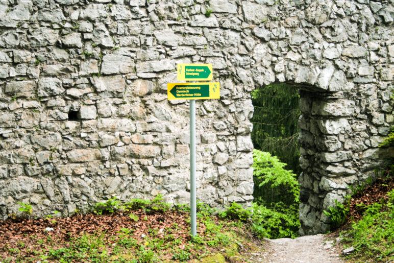 Ein Durchgang und Wanderwegweise in der Ruine