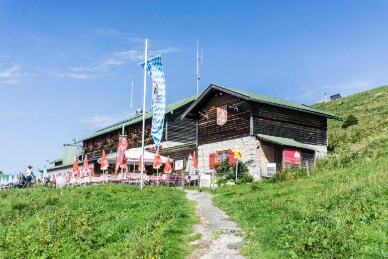 Die Alpenvereinshütte Brauneckhaus liegt nmittelbar neben der Bergstation und dem Gipfelkreuz