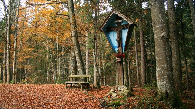 Das Wegkreuz im Wald mit erster Rastmöglichkeit