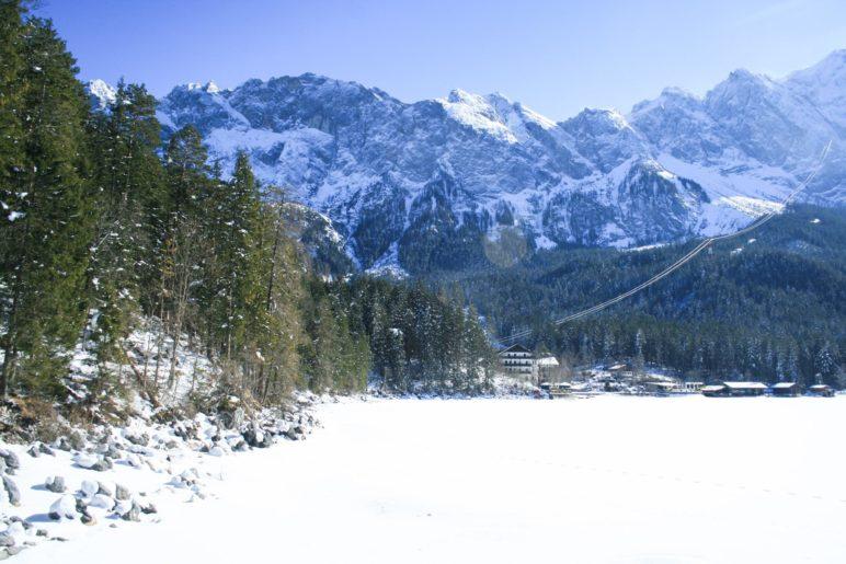 Der zugefrorene See, das Eibsee-Hotel und im Hintergrund das Wetterstein-Gebirge