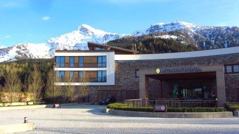 Das Hotel vor den noch verschneiten Bergen