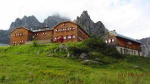 Die Hofpürglhütte vor der von Wolken umgebenen Bischofsmütze