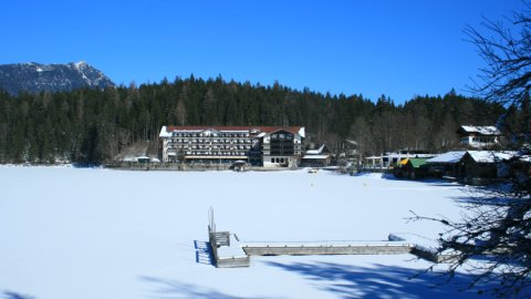 Das Eibsee-Hotel mit dem zugefrorenen See im Vordergrund