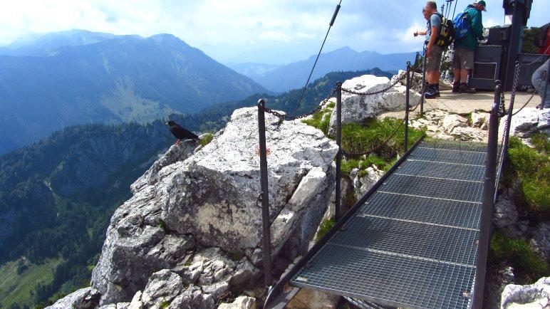 Über die kurze Brücke geht es zum 12 Meter hohen Gipfelkreuz der Kampenwand