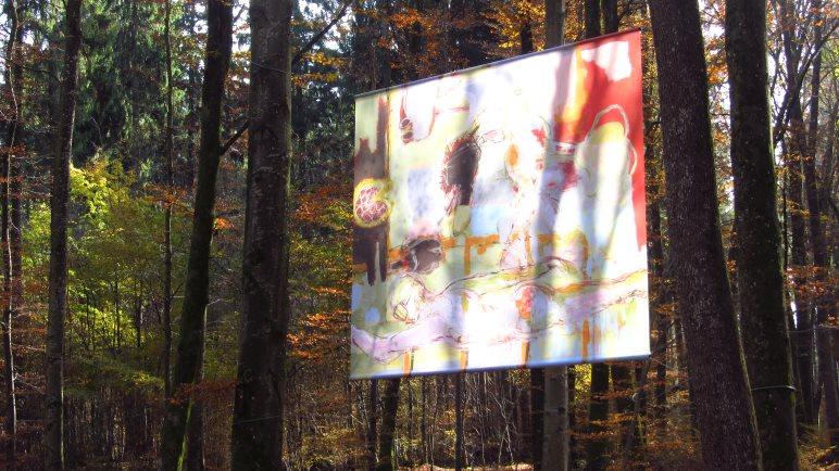 Ein riesiges Bild zwischen den Bäumen - wirkungsvoll in Szene gesetzt durch das Sonnenlicht