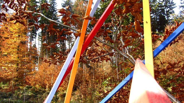 Farbige Stangen und buntes Herbstlaub auf dem Skulpturenweg St. Hubertus