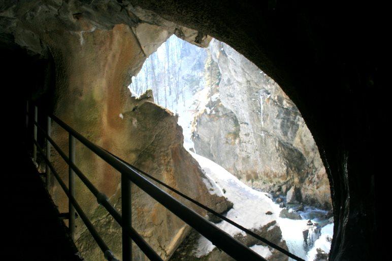 Ein Tunnelfenster am Ende des Klammwegs erlaubt den Blick auf die sonnendurchflutete Partnach