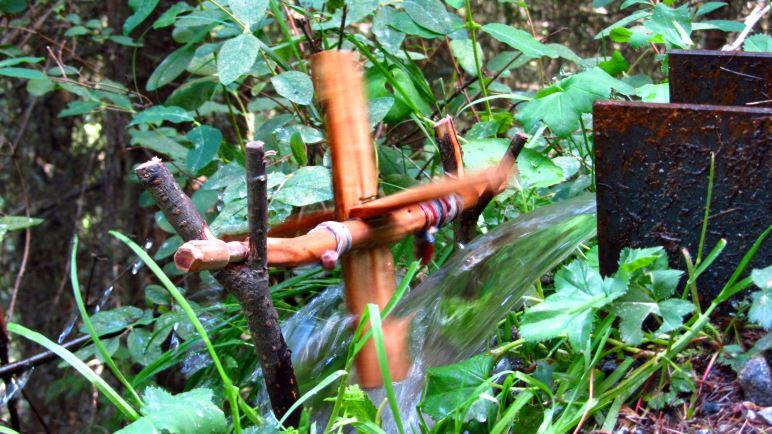 Ein kleines Wasserrad am Rand des Wanderwegs