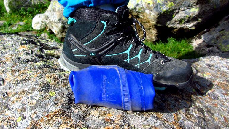 Ein eingerolltes Paar Onemoment Schuhe - verglichen mit Kinder-Wanderschuhen
