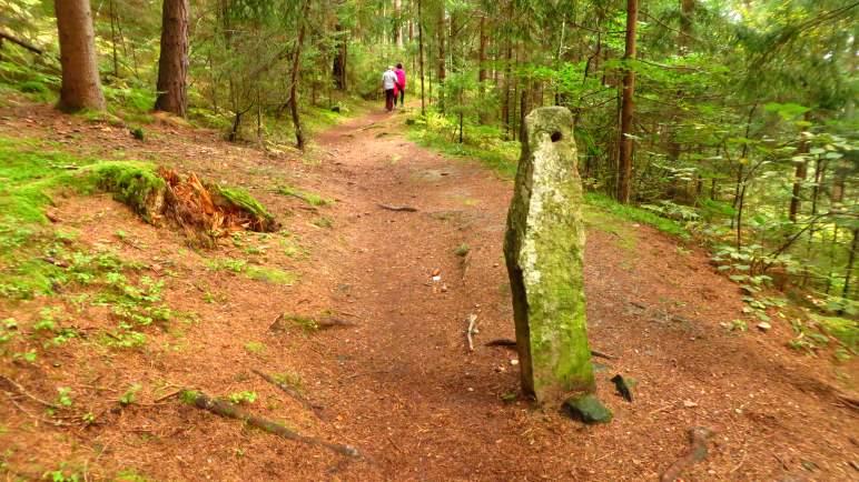 Ein Stein mit einem Loch, mitten auf dem Weg. Etwa hier ist der Abzweig ins Tal