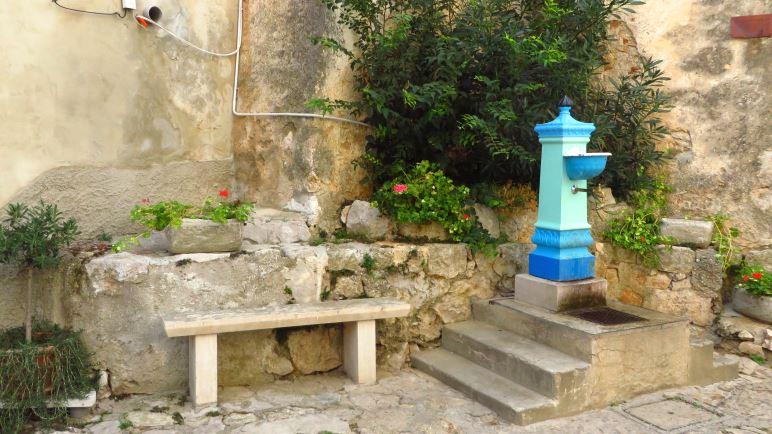 Der bunte Brunnen vor der Kirche ist das Wahrzeichen von Mošćenice