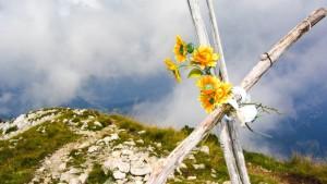 Das Gipfelkreuz der Cima delle Pozzette auf dem Monte Baldo über dem Gardasee. Mit bunten Plastikblumen als Schmuck.