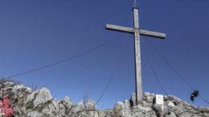Am Spitzsteingipfel. Direkt neben dem Gipfelkreuz markiert der Grenzstein die Grenze zwischen Deutschland und Österreich. Chiemgauer Alpen