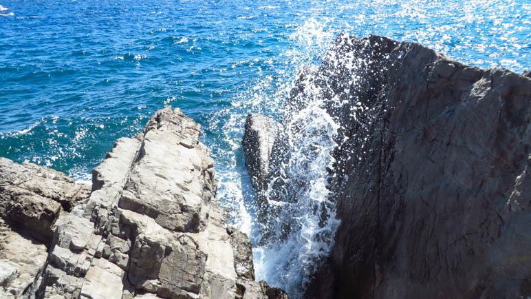 Die Gischt spritzt zwischen den Felsen hoch