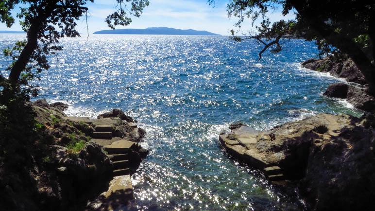 Eine kleine Felsbucht, im Hintergrund liegt die Insel Cres
