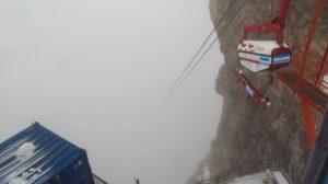 Eine Materialseilbahn der Baustelle. Die Seile verschwinden nach wenigen Metern im Nebel