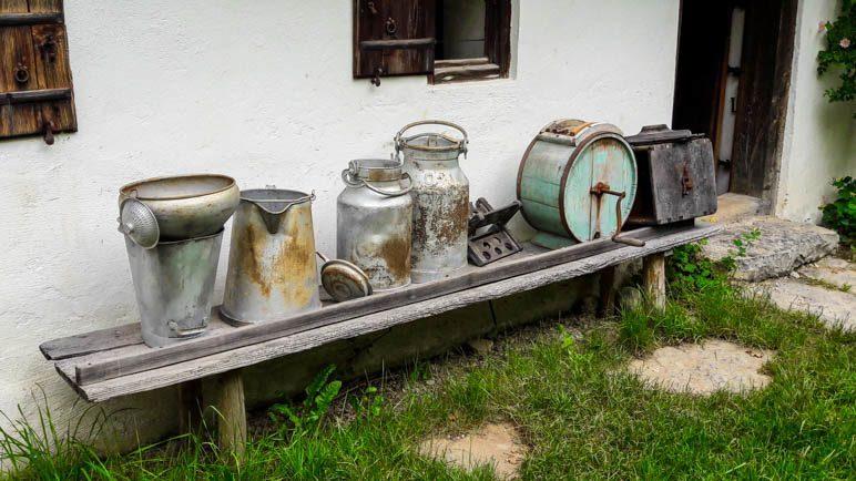 Milchkannen vor einem der Häuser des Freilichtmuseums Glentleiten