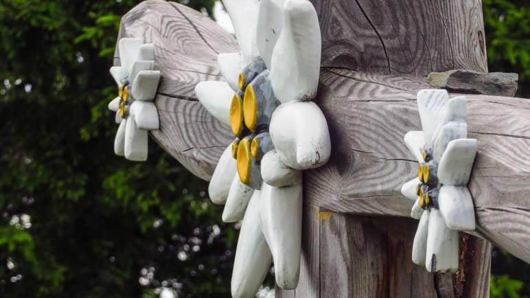 Vier geschnitzte Edelweisse schmücken das Kreuz des Lahngang-Gipfelkreuzes