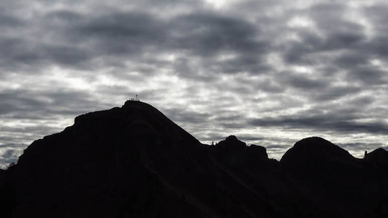 Der Gipfel der Rotwand als Schattenriss mit Gipfelkreuz und Wanderern