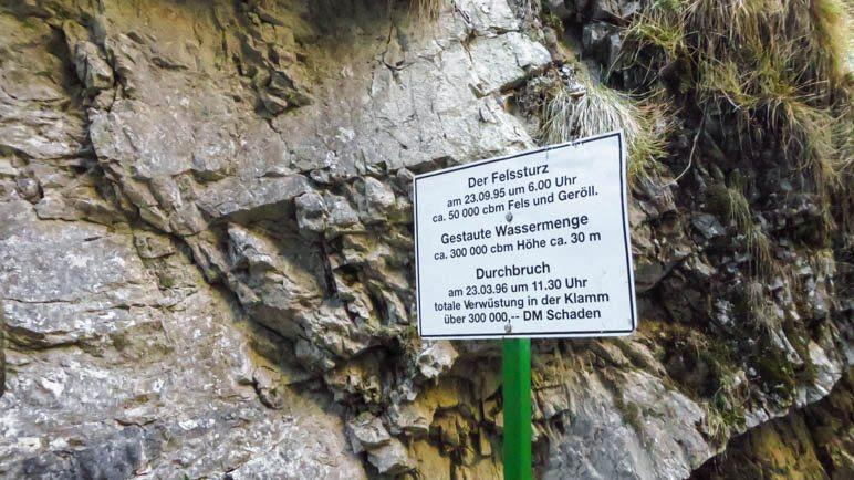 Das Schild, das über den Felssturz und den Dammbruch informiert