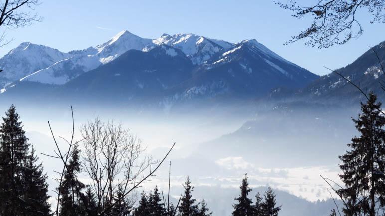 Das Tal liegt im leichten Nebel, darüber die Chiemgauer Berge