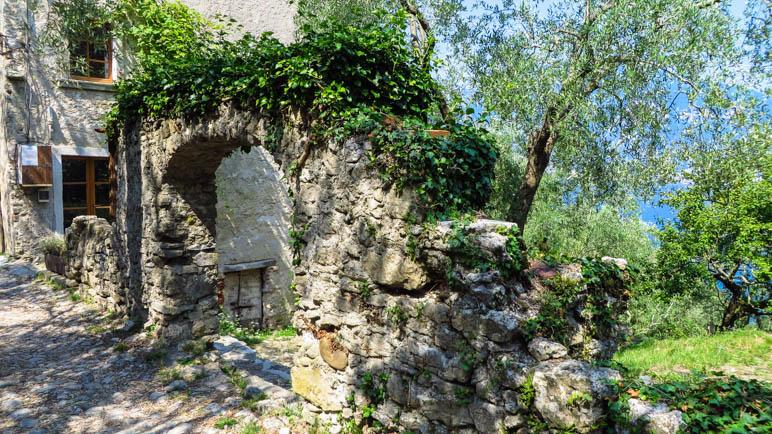 Ein Mauerfragment mit einem Torbogen im Dorf Campo di Brenzone