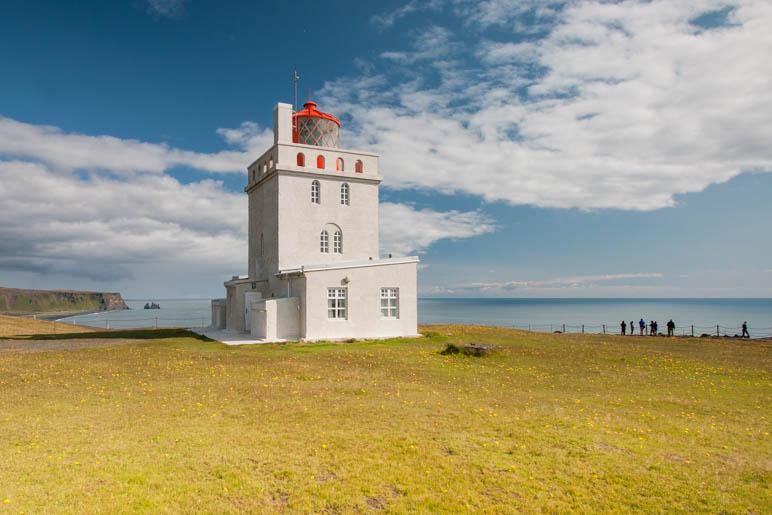 Der Leuchtturm am Kap Dyrhólaey. Links im Hintergrund die Reynisdrangar Felsen
