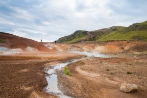 Wie aufgerissen wirkt die Landschaft am Seltún. Darüber die grünen Hügel