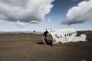 Ein motorisierter Paraglider fliegt um das Flugzeugwrack herum