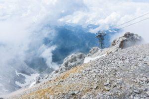 Ehrwald im Tal liegt in den Wolken. Der Stützpfeiler gehört zur Tiroler Zugspitzbahn