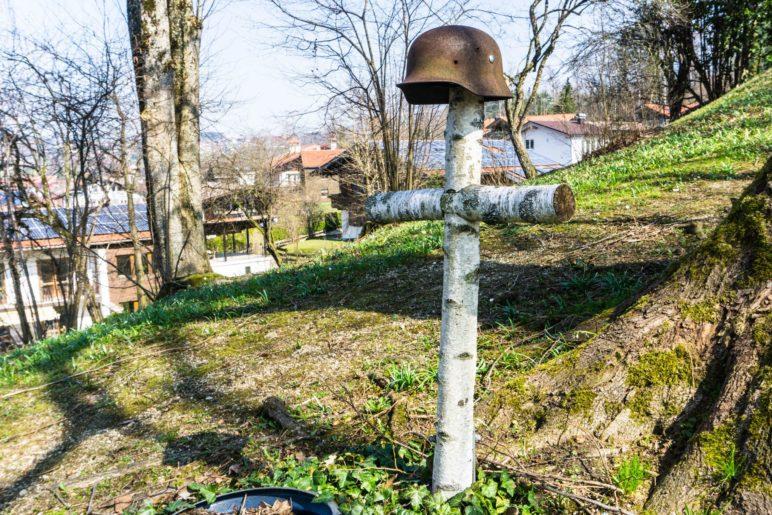 Das Kreuz aus Birkenstämmen mit dem Stahlhelm steht neben der Kriegerkapelle