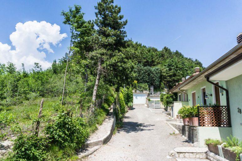 Links führt, direkt am Zaun, der schmale Weg bergauf