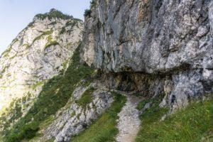 Der Weg führt unter einem Felsüberhang entlang