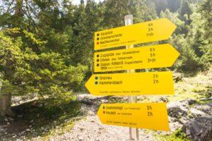 Ein Wegweiser an der Höllentalangerhütte. Unser weiterer Weg ist rot markiert