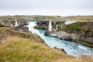 Die alte Brücke über den Skjálfandafljót, von der neuen Brücke aus gesehen. Im Hinntergrund ist die Gischt des Goðafoss zu sehen