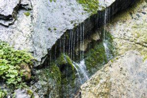 Wasservorhänge und Tropfenfäden auf der gegenüberliegenden Felswand