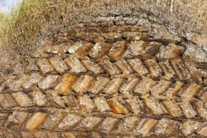 Eine Mauer aus geschichteten Torfziegeln