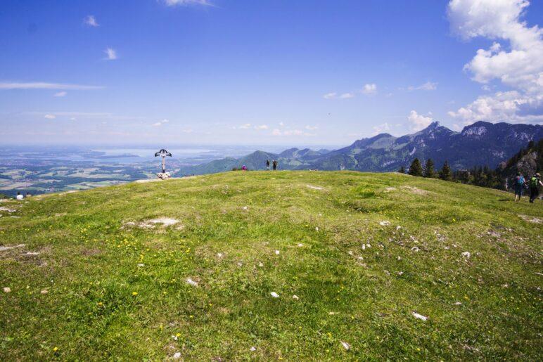 Gleich hinter dem Gipfelkreuz liegt der  Chiemsee, rechts die Kampenwand