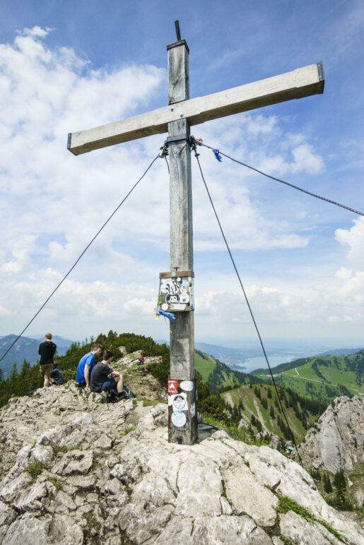 Am Gipfelkreuz des Risserkogel. Im Hintergrund liegt der Tegernsee